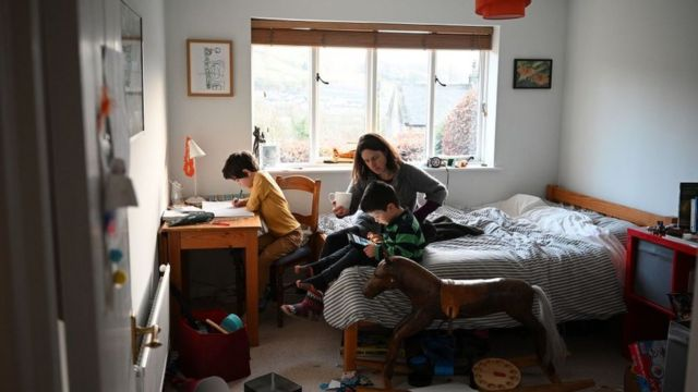 A mother with two children inside a room