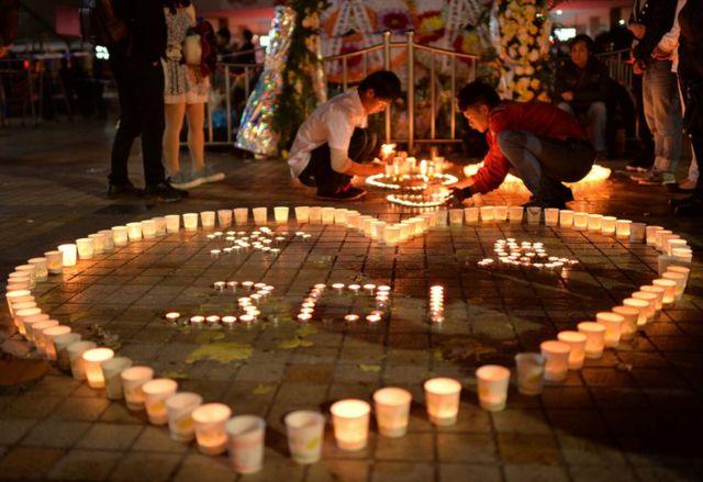 雲南省の鉄道駅でおきた刃物による襲撃事件の犠牲者を追悼しろうそくが並べられた(14年3月)