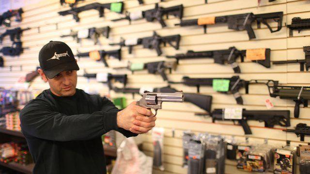 Gun salesman in Florida shows off merchandise
