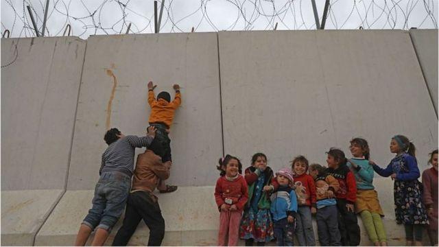 تصویری از ازدحام آوارگان سوری پشت دیوار مرزی ترکیه در ادلب