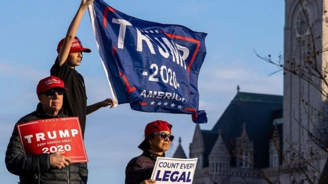 Manifestantes seguram cartazes pró-Trump