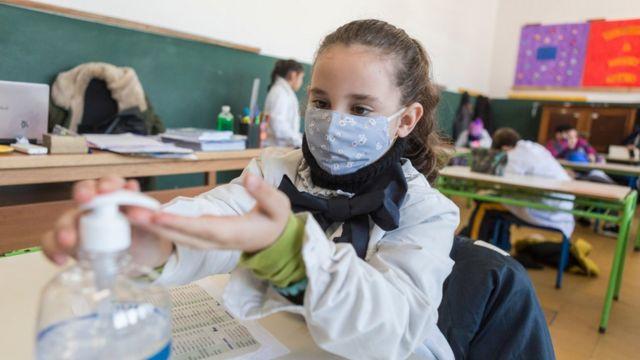 Una niña en una escuela en Uruguay con mascarillas poniéndose gel con alcohol en las manos