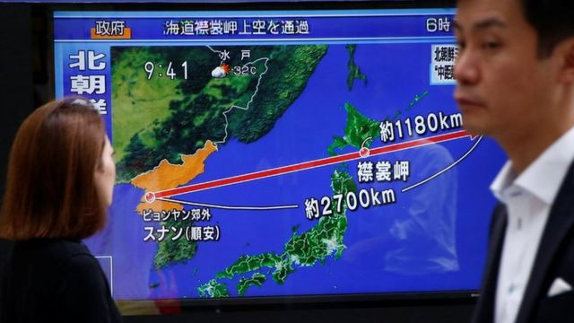 People walking in front of Japanese TV showing missile flight path