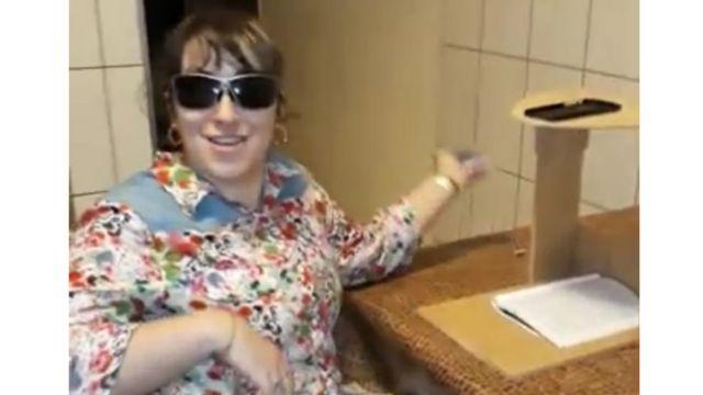 Foto de uma mulher que usa óculos escuros. Ao lado direito, uma mesa com um caderno e um suporte de madeira