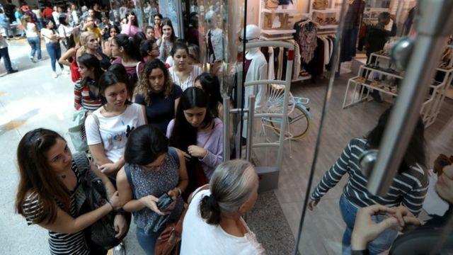 Grupo de personas haciendo fila delante de un comercio en Venezuela