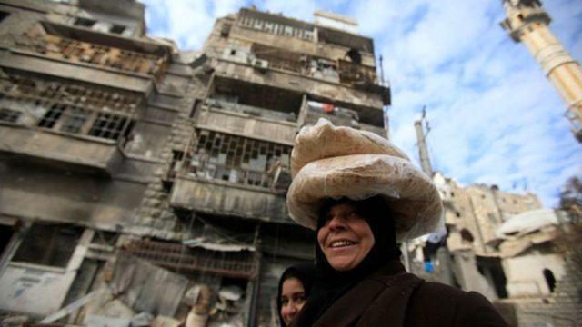 Mujer llevando pan en la cabeza en las calles de Alepo, Siria.