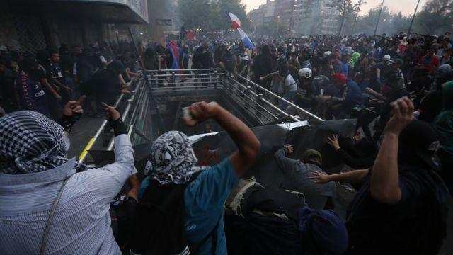 Pessoas jogando pedras durante protesto