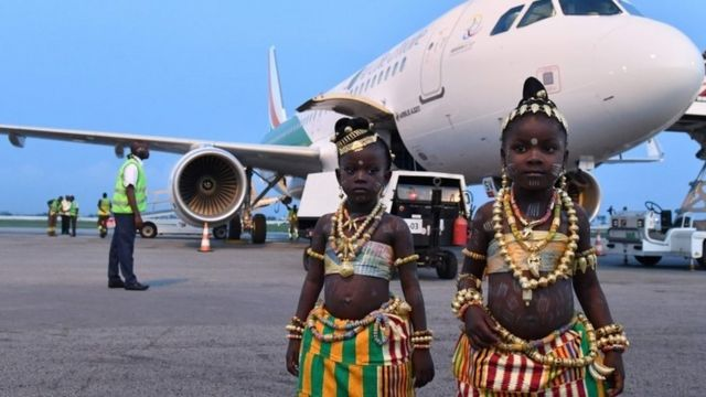 """Two young girls in traditional dress pose in front of the tenth airplane of Ivory Coast's national carrier Air Cote d""""Ivoire, a new generation Airbus A320, during a ceremony at Felix Houphouet-Boigny airport in Abidjan on July 18, 2017."""