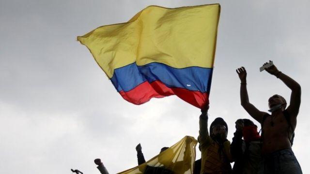 Manifestantes com bandeira colombiana