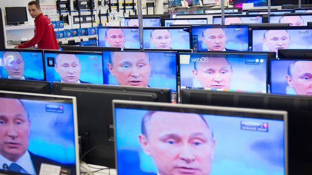 An employee stands by TV sets in a shop in Moscow during the broadcast of Russian President Vladimir Putin's annual televised phone-in with the nation.