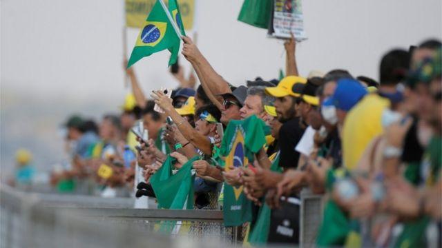 Pessoas com roupas verde, amarelo e azul atrás de cerca
