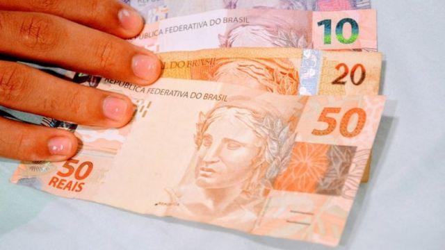 Mão segurando notas de R$ 50, R$ 20, R$ 10 e R$ 5