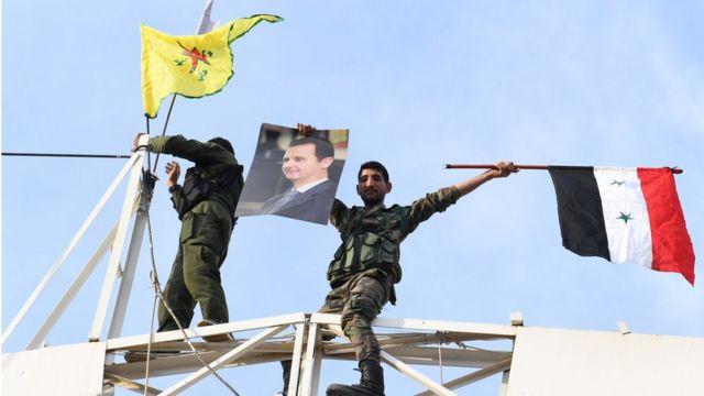 Suriye ordusunun Kobani'ye girmesinin ardından kentte Suriye ve YPG bayrakları yan yana görüntülenmişti