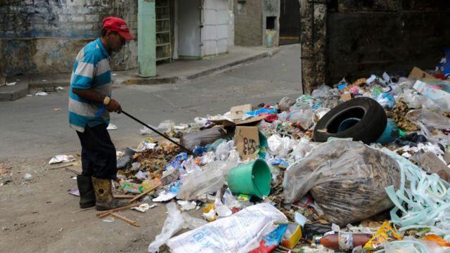 Un hombre revisa la basura en Venezuela.