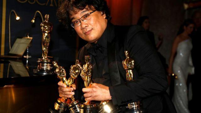 Bong Joon-ho segura várias estatuetas do Oscar