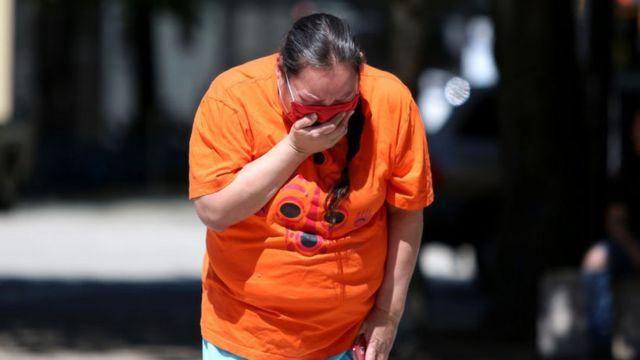 Una mujer llora frente a una vigilia en Canadá