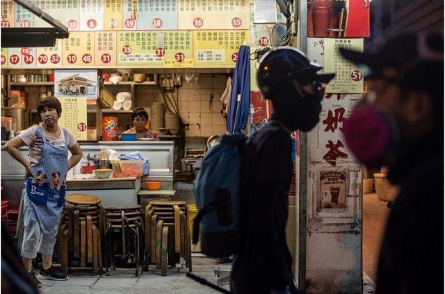 示威者走過一家灣仔街頭沒有生意的食肆。