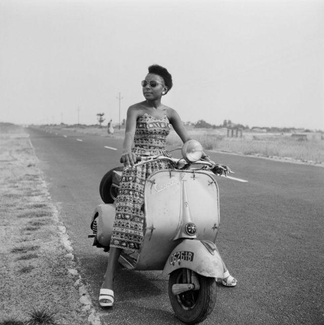 Une femme assise sur un cyclomoteur, au bord de la route, pose devant la caméra.