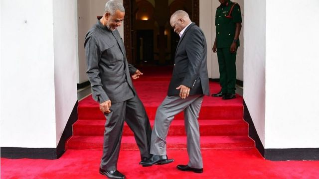 Tanzanian opposition politician Maalim Seif Sharif Hamad (L) by tapping his feet against theirs to avoid themselves from coronavirus in Zanzibar, Tanzania on March 03, 2020.