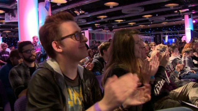 Stuart Main and other young people in audience at a gaming conference.