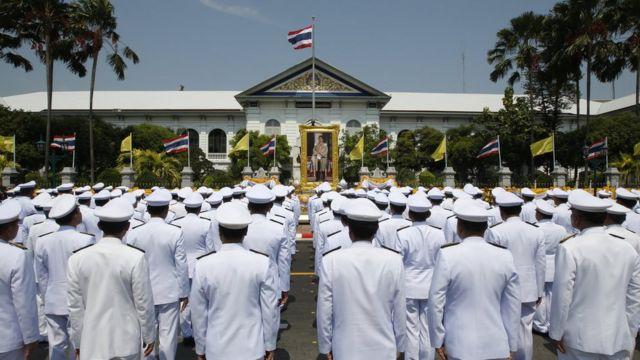 Bangkok officials standing in front of a portrait of Thai King Maha Vajiralongkorn Bodindradebayavarangkun