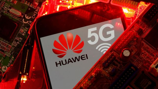 The Huawei and 5G logos are seen amid a pile of glowing red printed circuit boards (PCBs)