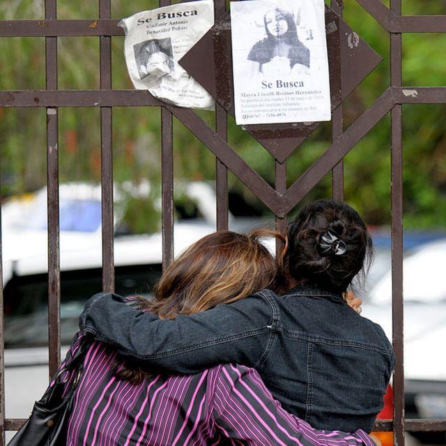 Dos mujeres esperan a las puertas de Medicina Legal, en San Salvador, información sobre las víctimas después de que unos pandilleros, según la policía, quemaran un autobús.