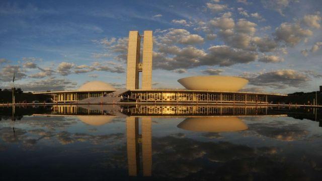 Prédio do Congresso refletido num espelho d'água sob um céu azul com nuvens