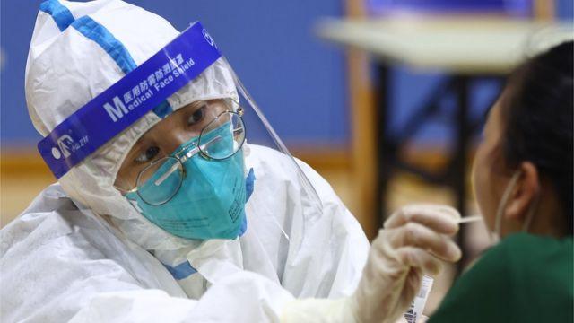 7月26日,南京市一处核酸检测点内,医务人员为市民进行核酸检测取样。