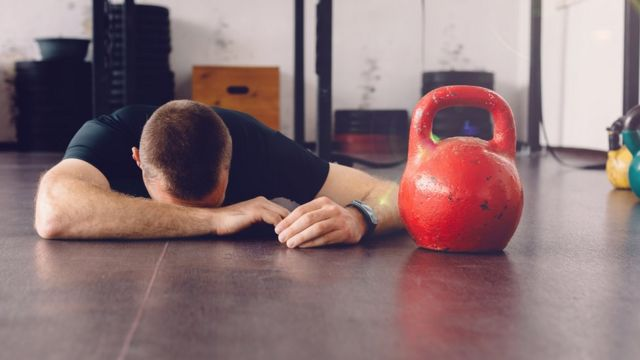 Un hombre visiblemente cansado en el gimnasio