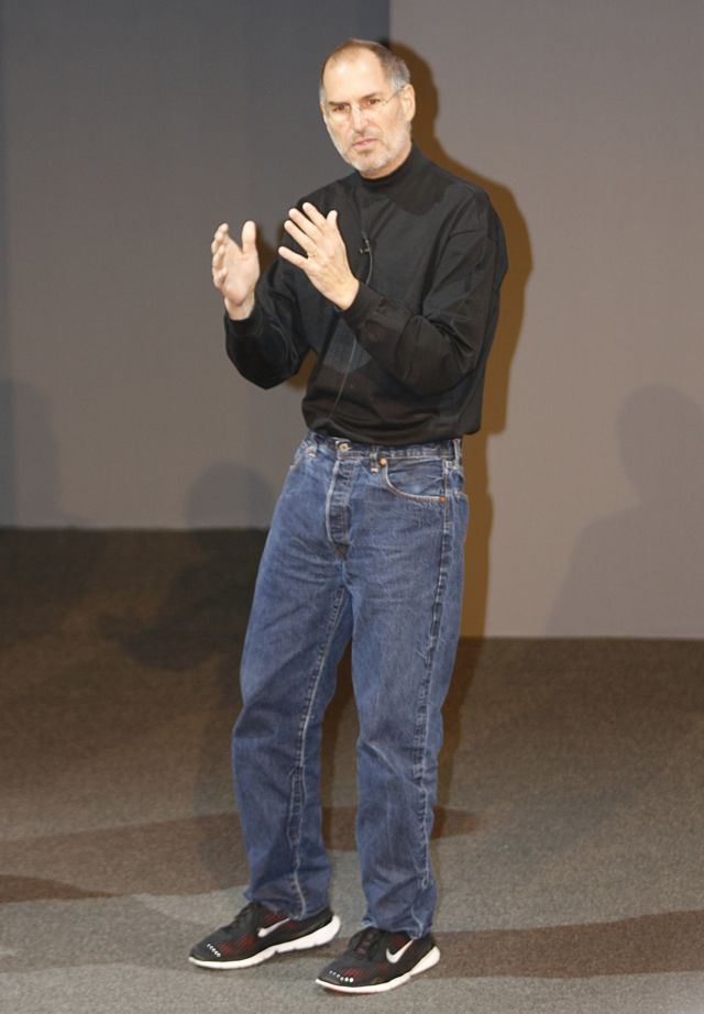 Steve Jobs vestido com suéter preto de gola alta, jeans e tênis em evento da Apple