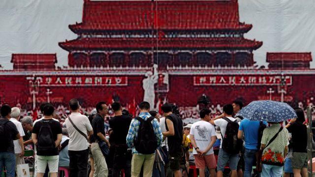 六四28周年晚会开始之前,维园群众站在象征1989年天安门广场的海报前。