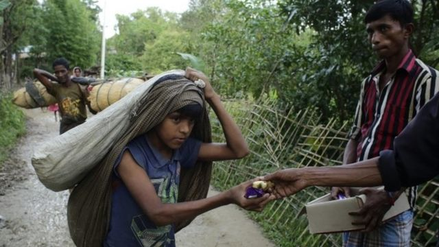 Rohingya refugees receive bread and bananas from local people as they arrive in Tuangiri, Teknaf, Bangladesh (12 September 2017)
