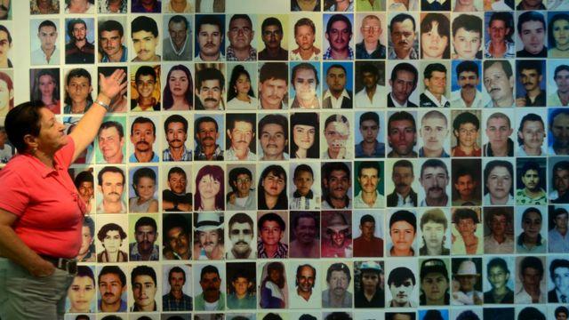 Una muer frente a un mural con fotos de víctimas del conflicto armado