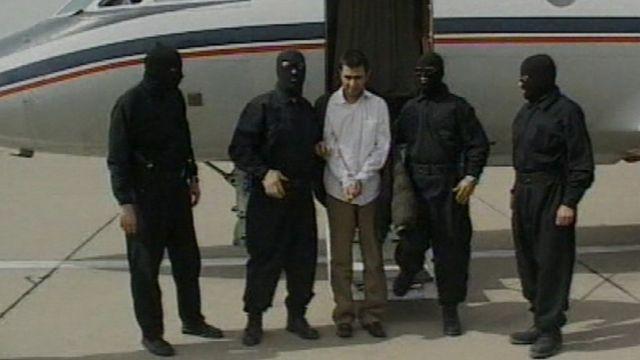Этот кадр показали 23 февраля 2010 на иранском государственном канале.  На нем лидер мусульман-суннитов Абдолмалик Риги в наручниках в окружении четырех мужчин в масках стоит перед небольшим самолетом