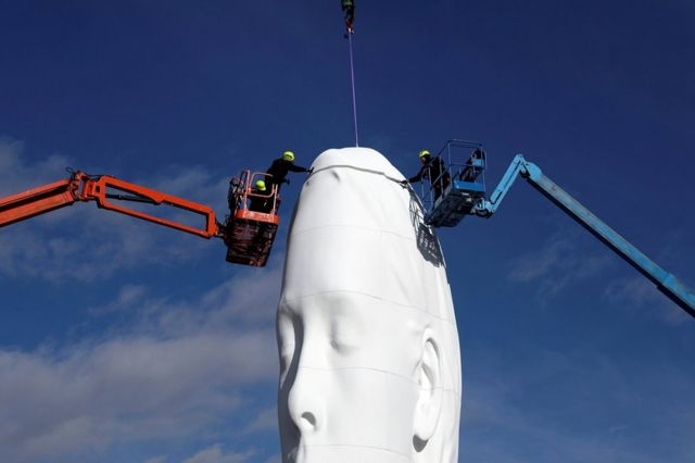 Workers put the finishing touches on a statue