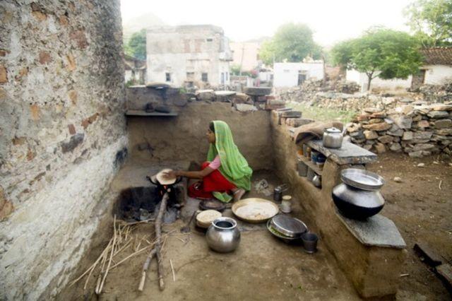 Une femme au foyer faisant des chapattis dans une cuisine ouverte dans le village de Delwara, Udaipur, Rajasthan, Inde.