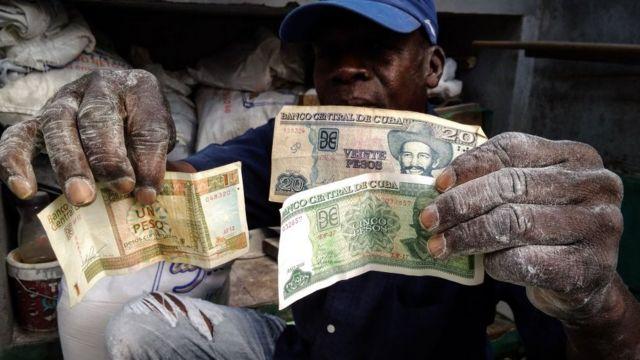 Homem mostra notas de pesos cubanos e os CUCs, a moeda dos turistas