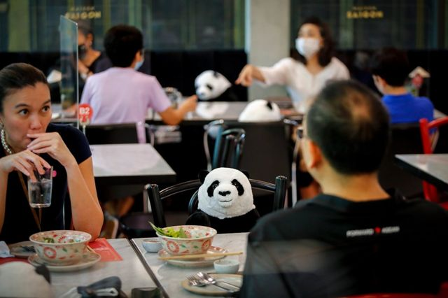 A stuffed panda is seen on a chair next to diners in a restaurant