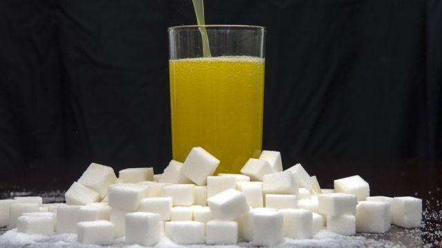 مشروب أصفر اللون في وب زجاجي فوق مكعبات السكر