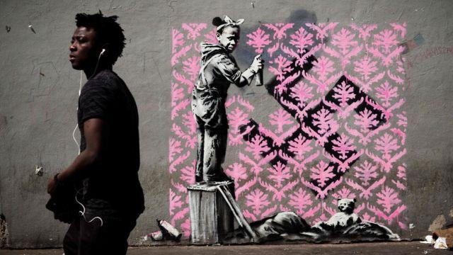 Čovek pored Benksijevog murala u Parizu.