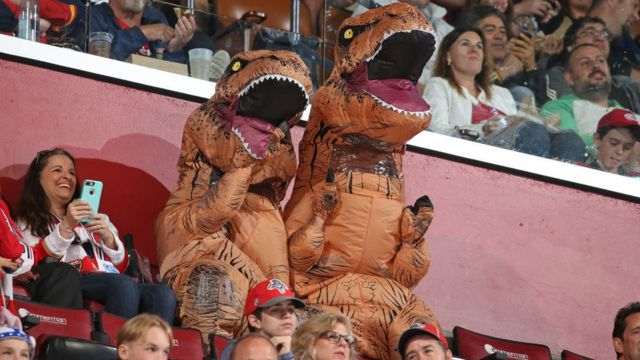 Dos personas disfrazas de dinosaurios