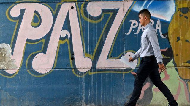 Un hombre pasa frente a un mural con la palabra paz en Colombia