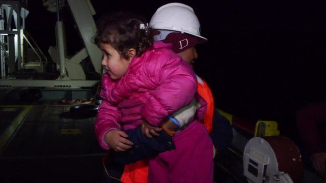Girl is carried aboard a rescue boat
