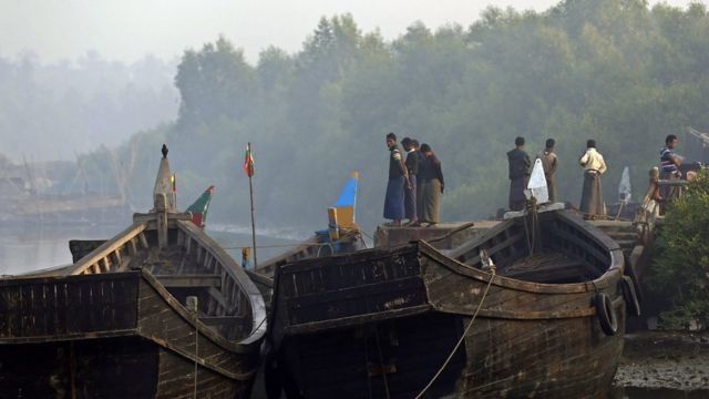 Muslim people stand near the boat near the Border Check Point of Maungdaw town, Bangladesh-Myanmar border, Rakhine State, western Myanmar, 22 December 2016