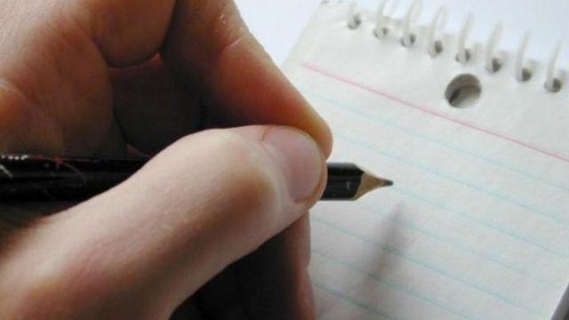 Mão esrevendo em caderno