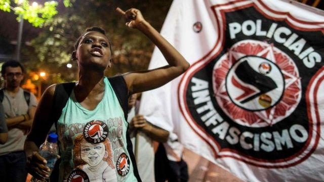 """Manifestante com cartaz atrás dizendo """"policiais antifascismo"""" em protesto contra Bolsonaro"""