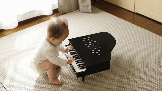 Bebê mexe em um piano de brinquedo