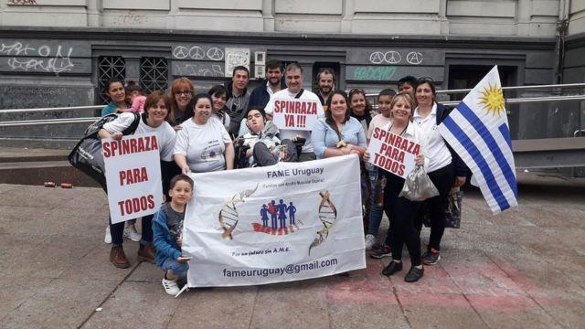 """Marcha en Uruguay de familiares de pacientes de AME con carteles que dicen """"Spinraza para todos"""" y """"Spinraza ya"""""""