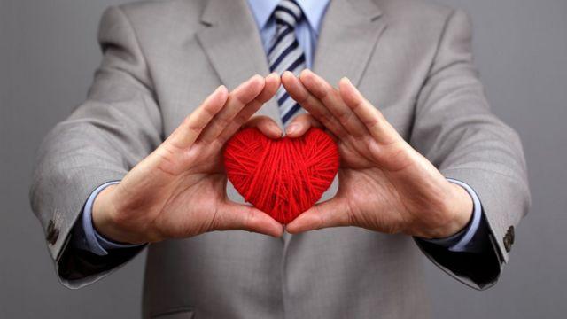 Hombre con un corazón de lana en la mano.